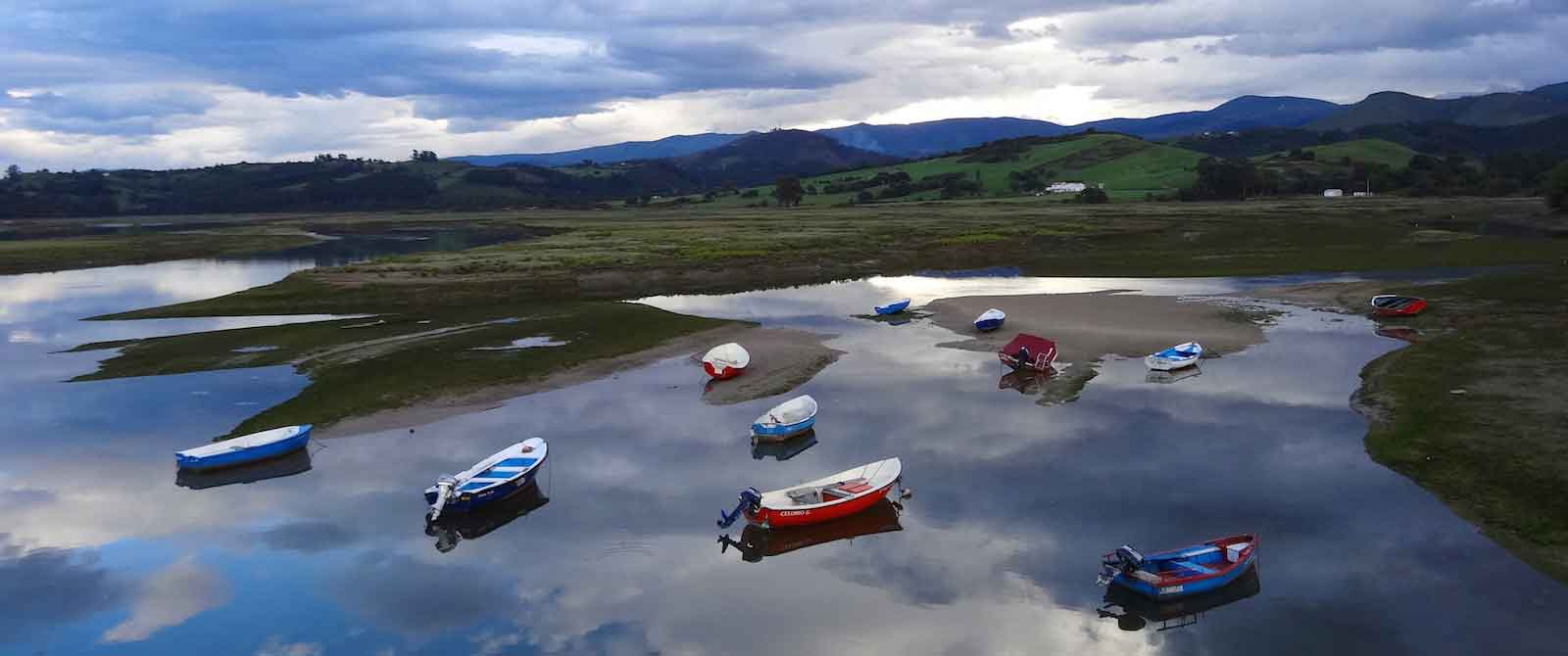Fishing boats on still water in Cantabria on green coast of Spain